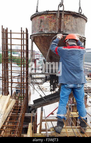 construction workers pouring concrete in form - Stock Photo