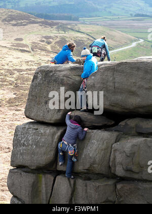 Group of people rock climbing in the Peak District National Park Derbyshire England - Stock Photo