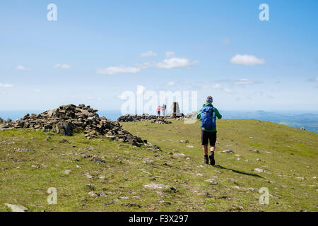 Hikers approaching trig point cairn on Moel Hebog mountain summit in mountains of Snowdonia National Park, North - Stock Photo