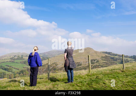 Two walkers looking at a view to Roundton fort from Todleth Hill, Churchstoke or Church Stoke (Yr Ystog), Montgomery, - Stock Photo