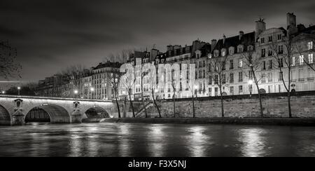 Seine River, Quai de Bourbon on Ile Saint Louis with Pont Marie and evening lights. Row of 19th century buildings, - Stock Photo