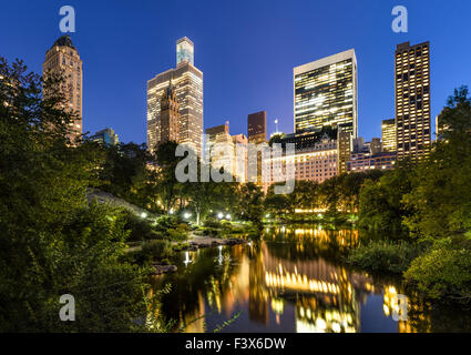 Manhattan skyscrapers illuminated in early evening light. The buildings reflect in the Central Park Pond. New York - Stock Photo