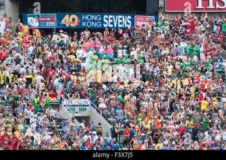 Crowds of fans wearing costumes in the south stand of Hong Kong Stadium Sevens Rugby event. - Stock Photo