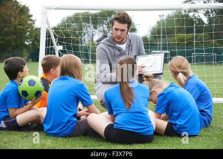 Coach Giving Team Talk To Elementary School Soccer Team - Stock Photo