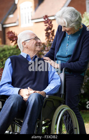 Senior Man In Wheelchair Being Pushed By Wife - Stock Photo