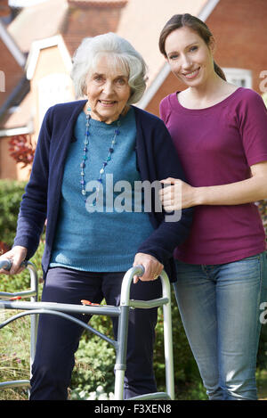 Daughter Helping Senior Mother To Use Walking Frame - Stock Photo