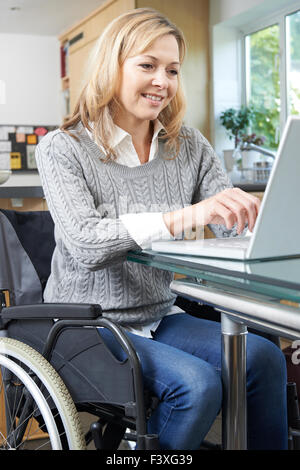 Disabled Woman In Wheelchair Using Laptop At Home - Stock Photo