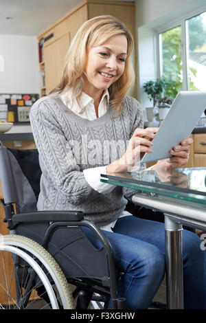 Disabled Woman In Wheelchair Using Digital Tablet At Home - Stock Photo