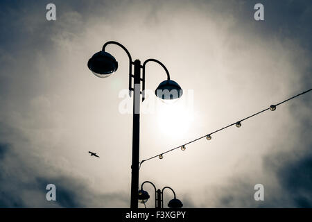 Street lighting and seaside illuminations seen at the end of the tourist season seen against an overcast moody sky. - Stock Photo