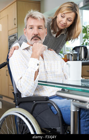 Woman Comforting Depressed Man In Wheelchair At Home - Stock Photo