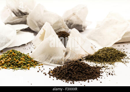 Small piles of different types of tea on plain white background with some teabags scattered betweem them. Japanese - Stock Photo