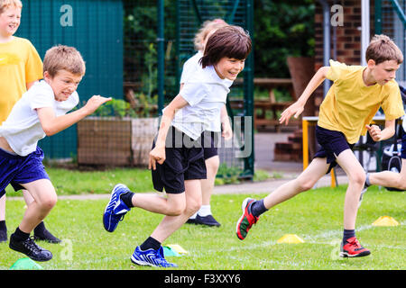 England, school children, boys, 10-11 year old, running race on outdoor grass track. Wearing shorts and t shirt, - Stock Photo