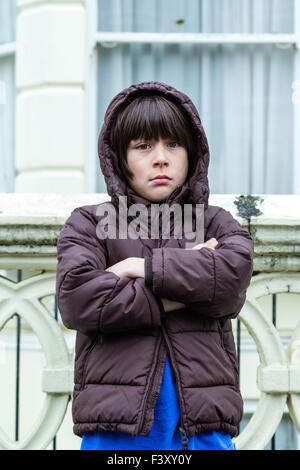 Caucasian child, boy, 9-10 year old, standing outside, wearing anorak, cold, arms folded, waiting, unhappy expression - Stock Photo