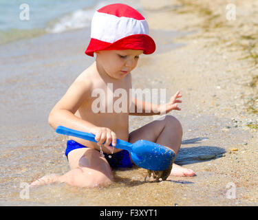 Little boy playing in shallow surf - Stock Photo