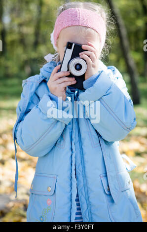 Small girl playing with an slr camera - Stock Photo