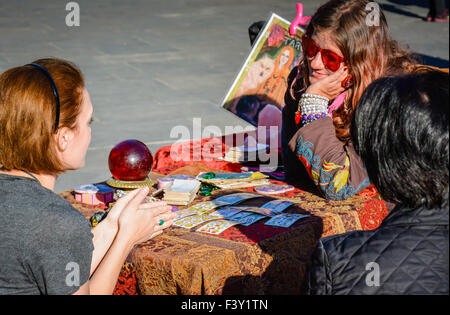 Fortune teller reads tarot cards to client with crystal ball nearby in Jackson Square in the French Quarter, New - Stock Photo
