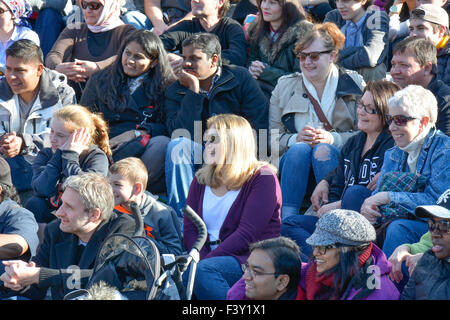A crowd of diverse people in the USA sitting on bleachers reacting and watching an event - Stock Photo