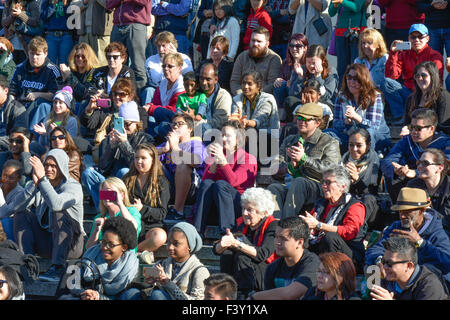 Crowd of diverse people in the USA sitting on bleachers reacting and watching an event - Stock Photo