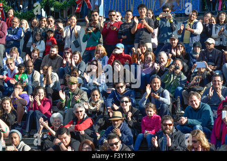 Crowd of ethnically diverse people of all ages, in the USA, some sitting,  some standing while laughing & applauding - Stock Photo