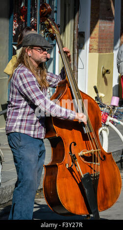 Street Musician wearing a flat cap plays a stand up bass on a crowded street in the French Quarter in New Orleans, - Stock Photo