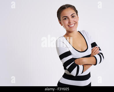 Vivacious confident pretty young woman standing with folded arms giving the camera a lovely smile, upper body on - Stock Photo