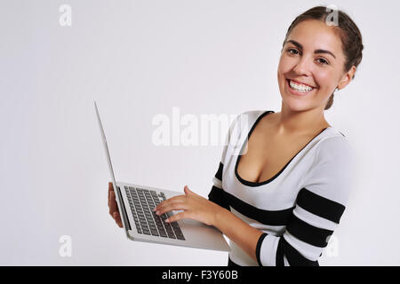 Happy smiling young woman using a handheld laptop computer to browse the internet looking at the camera with a warm - Stock Photo