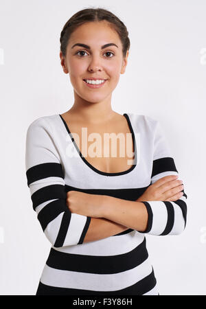 Stylish young woman in a striped top standing with her arms folded looking at the camera with a friendly smile - Stock Photo