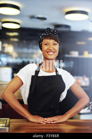 Confident successful young small business owner standing behind the counter in her coffee shop giving the camera - Stock Photo