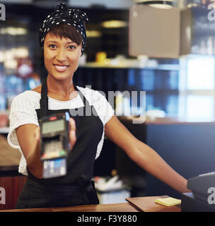 Young shop owner requesting payment holding out a handheld banking machine for a customer to enter the code for - Stock Photo