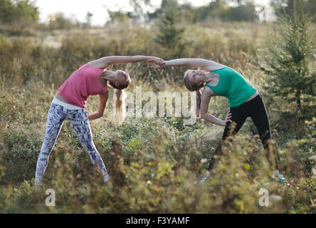Two supple young women working out together - Stock Photo