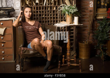 Young woman sits in an armchair - Stock Photo