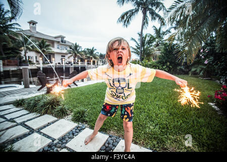 A young boy with sparklers wearing a cool dude t-shirt. - Stock Photo