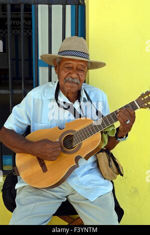 Old Cuban musician playing acoustic guitar solo on a street corner in Old Havana Cuba - Stock Photo