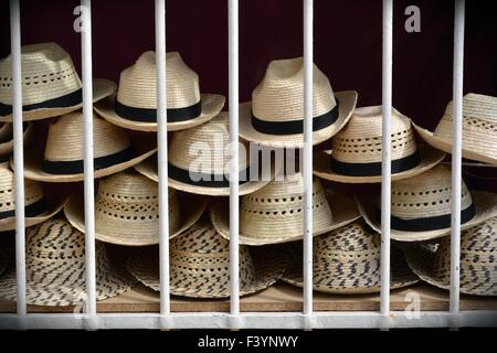 Straw hats for sale stacked behind the window grill on a street in Trinidad, Cuba - Stock Photo