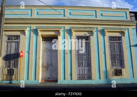 pastel turquoise and yellow facade of old colonial building, Santa Clara, Cuba with caged windows, white door and - Stock Photo