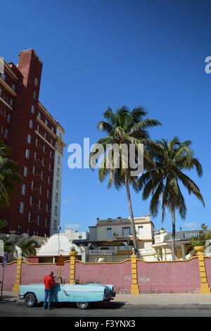Havana street in Vedado with cloudless blue sky high rise building palm trees and vintage open top car and driver - Stock Photo
