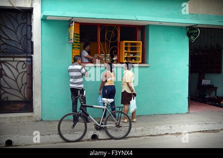 some locals ordering at a hole in the wall snack bar in a back street in Santa Clara Cuba with a bicycle parked - Stock Photo