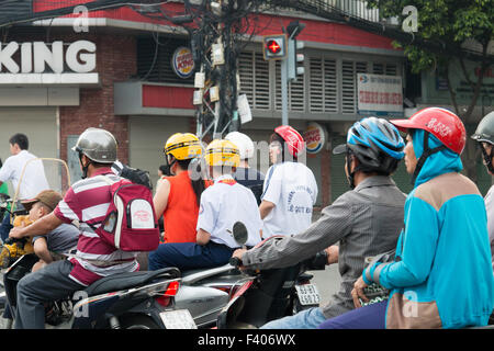 scooter riders in Ho Chi Minh city centre including father in striped top whose son is sleeping on a bear whilst - Stock Photo