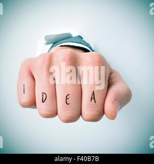 a young businessman breaks through a wall with his fist, and the word idea written in his knuckles - Stock Photo