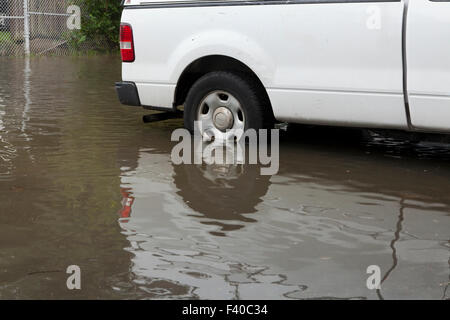 Car wheel partly submerged in floodwater - USA - Stock Photo
