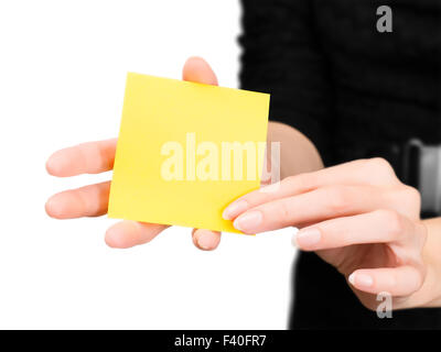 Beautiful woman hands with blurred silhouette holding blank yellow memo stick. Isolated on white with clipping path - Stock Photo