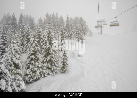 Chairlift in snowfall at alpine ski resort - Stock Photo