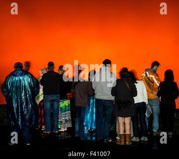 Visitors in silhouette at dusk, lava glowing Kilaueea Caldera volcano, Hawai'i Volcanoes National Park, Big Island, - Stock Photo