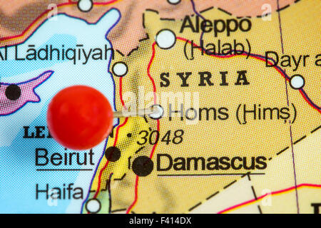 Close-up of a red pushpin in a map of Homs, Syria. - Stock Photo