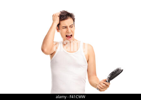 Angry young man loosing hair and holding a hairbrush isolated on white background - Stock Photo