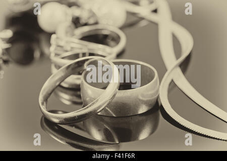 gold wedding rings, earrings and chains - Stock Photo
