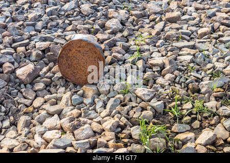 Trash metal on the rocky shore rust polluting nature - Stock Photo