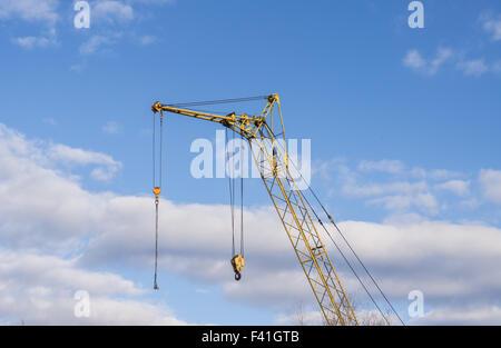 Mobile crane boom against the blue sky - Stock Photo