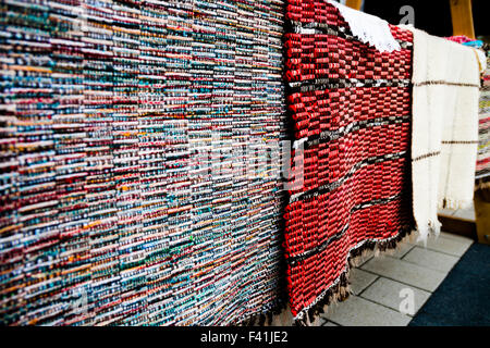 Traditional handmade rugs being displayed on a stand, on a market in Miercurea-Ciuc, Romania - Stock Photo