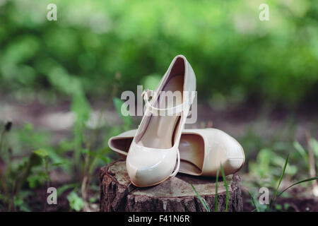 Picture of female white wedding shoes on green grass - Stock Photo